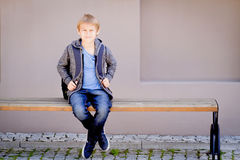 Boy with backpack sitting on the bench near the school royalty free stock photos