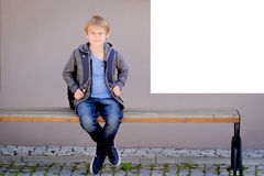 Boy with backpack sitting on the bench near white mock up poster on school wall Stock Photos