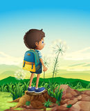 A boy with a backpack standing above a stump Stock Images