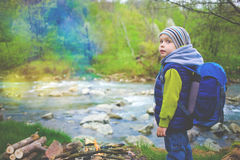 A boy with a backpack standing on the bank of the river. Little boy with a backpack standing in a forest near a mountain river, a fire is burning on the Royalty Free Stock Photo