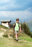 Boy with backpack and trekking poles in mountains Stock Images