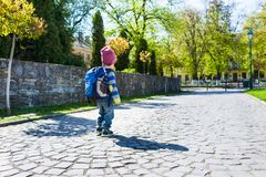 A boy with a backpack walking across the street. A small child in a striped sweater goes through the city Stock Images
