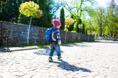 A boy with a backpack walking across the street. A small child in a striped sweater goes through the city Stock Photography