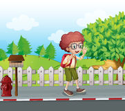 A boy with a backpack walking near the mailbox Royalty Free Stock Photos