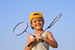 Boy with badminton rackets. Boy with two badminton rackets outdoors Royalty Free Stock Photos