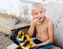 Boy with a bag of chips in the yard of the rural house Royalty Free Stock Photography