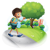 A boy with a bag walking along the street Royalty Free Stock Photos