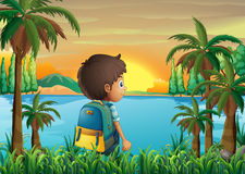 A boy with a bag watching the sunset Royalty Free Stock Photo
