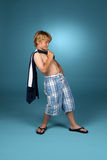 Boy in baggy blue plaid shorts. With his shirt slung over one shoulder Royalty Free Stock Photo