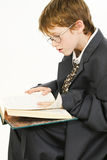 Boy in Baggy Suit Reading Royalty Free Stock Images