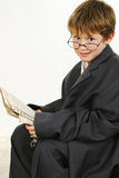 Boy in Baggy Suit Reading Newspaper Royalty Free Stock Photos