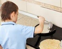 Boy bakes pancakes Royalty Free Stock Images