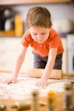 Boy baking cookies Stock Photos
