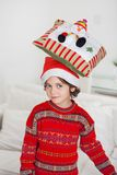 Boy Balancing Cushion On Head During Christmas. Cute boy looking away while balancing cushion on head at home during Christmas royalty free stock photo