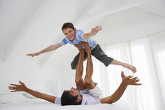 Boy Balancing On Father's Legs In Bedroom Stock Photo