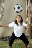 Boy balancing football on his head Royalty Free Stock Photos