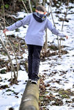 Boy balancing on log in the winter Stock Images
