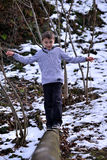 Boy balancing on log in the winter Royalty Free Stock Photography