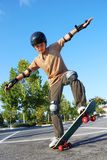Boy Balancing on Skateboard. Teenage boy balancing on a skateboard in a parking lot on a sunny day with blue sky and trees in the background Royalty Free Stock Images