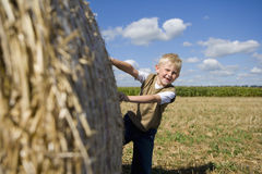 Boy (9-11) by bale of hay in field, smiling, portrait Royalty Free Stock Photos