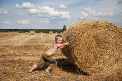 Boy with bale of straw Stock Photo