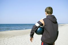 Boy with ball on beach. A boy standing on a beach, with a blue ball under his arm, looking away on the horizon. Empty beach, clear horizon, sunny weather Stock Images