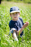 Boy in ball cap sitting in grass. Six year old boy wearing a ball cap sitting in a grassy field with a serious expression Stock Photo