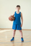 A boy with the ball. A caucasian boy in blue shirt holding backet ball Royalty Free Stock Photo