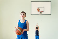A boy with the ball. A caucasian boy in blue shirt holding backet ball Stock Image