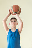 A boy with the ball. A caucasian boy in blue shirt holding backet ball Stock Photography