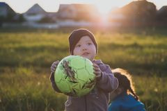 Boy with ball on the field with green grass stock image