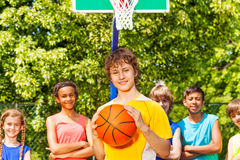 Boy with ball and international friends behind Stock Photography