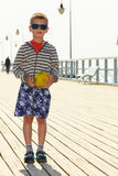 Boy with ball on pier. Stock Image