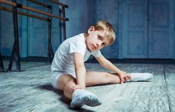 Boy ballet dancer at dance class. Boy ballet dancer doing exercise and stretching at dance class near the barre indoors royalty free stock photo