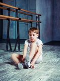 Boy ballet dancer at dance class. Boy ballet dancer putting on pointes at dance class near the barre indoors royalty free stock images