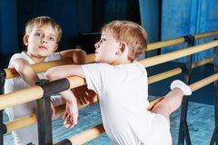 Boy ballet dancer doing exercise. At dance class near the barre indoors stock photos