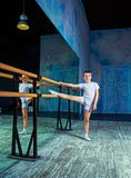 Boy ballet dancer doing exercise at dance class. Near the barre indoors stock photography