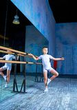 Boy ballet dancer doing exercise. At dance class near the barre indoors stock photography