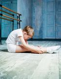 Boy ballet dancer doing exercise at dance class. Boy ballet dancer doing exercise and stretching at dance class near the barre indoors royalty free stock photography