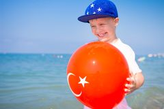 Boy with balloon Turkey flag on blue sea beach royalty free stock images