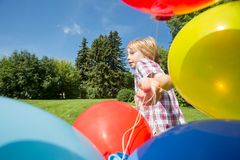 Boy With Balloons Running In Park Stock Photo