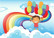 A boy with balloons standing near the rainbow Stock Images