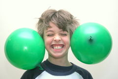 Boy with balloons stuck to his head. Smiling boy with green balloons stuck to his hair Royalty Free Stock Image