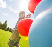 Boy With Balloons Walking In Green Meadow Royalty Free Stock Image