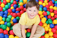 Boy and balls. Happy lad seated on colorful balls and looking at camera with smile Stock Images