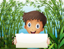 A boy at the bamboo farm holding an empty signage Stock Images