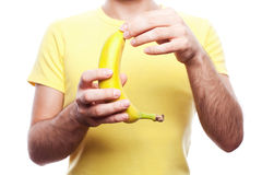 Boy with banana. Guy holding and opening yellow banana over white background. Healthcare concept. studio shot royalty free stock photography