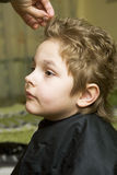 The boy in the barber shop. He gets the hair Royalty Free Stock Photography