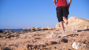 Boy barefoot running at the beach at morning exersises stock video footage