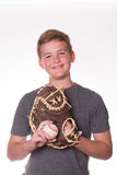 Boy with baseball and glove. Boy smiling while holding a baseball and glove royalty free stock photos
